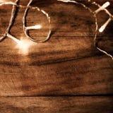 Ghirlanda d'ardore delle luci di Natale su un vecchio parque di legno antico Fotografia Stock
