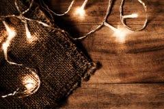 Ghirlanda d'ardore delle luci di Natale su un vecchio parque di legno antico Fotografia Stock Libera da Diritti