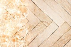 Ghirlanda d'ardore delle luci di Natale su un vecchio parque di legno antico Immagini Stock