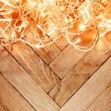 Ghirlanda d'ardore delle luci di Natale su un vecchio parque di legno antico Immagine Stock