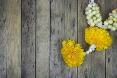 Ghirlanda del fiore del tagete sulla plancia di legno Immagine Stock
