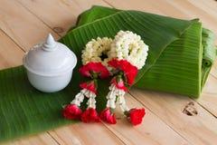 Ghirlanda del gelsomino dei fiori sul fondo della foglia della banana Fotografie Stock