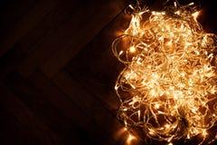 Ghirlanda delle luci di Natale su fondo scuro Cartolina di Natale con Fotografie Stock