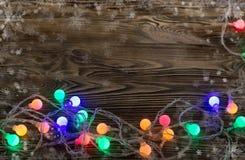 Ghirlanda illuminata su una tavola di legno Fotografie Stock Libere da Diritti