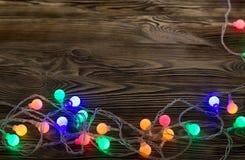 Ghirlanda illuminata su una tavola di legno Immagine Stock Libera da Diritti