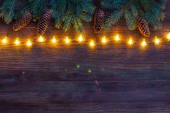 Ghirlanda scintillante di Natale con i rami dell'albero e dei coni di abete sui precedenti di legno Immagini Stock