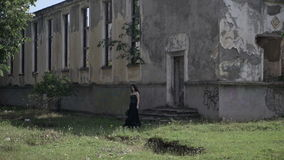 Ghost of beautiful young lady dressed in a gothic black clothes exiting a haunted ruined palace. Ghost of beautiful young lady dressed in gothic black clothes stock video