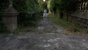 The ghost of the bride wanders through the ruins of the old castle. Bride of the Zombie. 4 k. Slow-motion shooting. The ghost of the bride wanders through the stock video footage