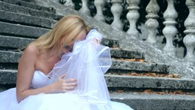 The ghost of the bride wanders through the ruins of the old castle. Bride of the Zombie. 4 k. Slow-motion shooting. The ghost of the bride wanders through the stock footage