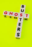 Ghost busters. Text ' ghost ' and ' busters ' inscribed on small white cubes in uppercase letters and arranged crossword style with common letter ' s ' , yellow Stock Photo