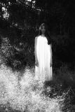 Ghost covered with a white ghost sheet on a rural path. Grainy textured image Stock Photos