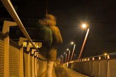 Ghost d'un homme et d'un chien sur un pont piétonnier la nuit Photos stock