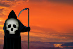 Ghost of death. Dramatic bloody sky background. The death figure wearing black hood with scull and looking on the bloody dramatic sky. Concept. The sky area is Royalty Free Stock Photos