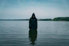 Ghost está na água em um casaco preto na tarde O fantasma olha assustador fotografia de stock