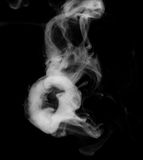 Ghost face. A ghostly face pattern composed of smoke rings; black and white on black background Royalty Free Stock Image