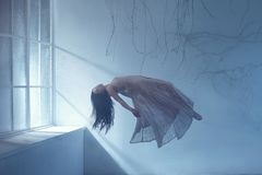A ghost girl with long hair in a vintage dress. A photograph of levitation resembling a dream. A dark Gothic room with. Branches and a huge window of flooded royalty free stock photography