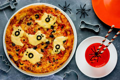 Ghost Halloween pizza, funny pizza decorated with cheese and oli Stock Image