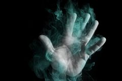 Ghost hand in smoke. On a black background royalty free stock photography