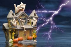 Ghost house. A ceramic ghost house with added lightning,cloud and water effects Royalty Free Stock Photography