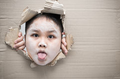 Ghost kid and looking through hole on cardboard. Halloween day concept. Copy space Royalty Free Stock Photo