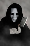 Ghost Killer man in mask and hood hold chopping knife, costume for Halloween night Stock Photography