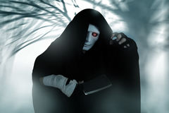 Ghost Killer man in mask and hood hold chopping knife, costume for Halloween night Stock Photo