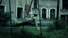 The ghost of a little girl on a swing in the old ruined house. evil spirit stock video footage