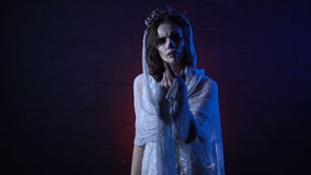 Ghost of lonely dead bride in white wedding dress and veil standing with sad face moving her hand. Scary girl halloween stock video