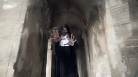 The ghost of a nun walks through the ruins of an old monastery. 4 k. Slow-motion shooting