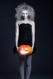 Ghost with orange pumpkin. Portrait of ghost with orange pumpkin over dark background stock image