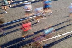 Ghost Runners. A group of marathon runners head away from the rising sun during the opening stages of a race stock image