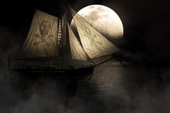 Ghost Ship. Evil Haunting And Mysterious Image Of A Ghostly Ship With Skull And Crossbones Mast Sailing Through Fog And Mist Under A Full Moon Night Sky Stock Photography