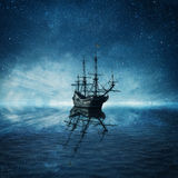Ghost ship. A ghost pirate ship floating on a cold dark blue sea landscape with a starry night sky background and water reflection Stock Photography