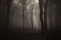 Ghost silhouette in dark mysterious forest with fog on Halloween. Night stock photo