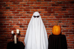 Ghost in sunglasses posing over brick background. Halloween party. Stock Photos
