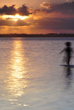 Ghost at sunset. A child plays in the pacific ocean at sunset Royalty Free Stock Images