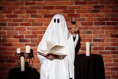 Ghost tenant le livre et le vin au-dessus du fond de brique Réception de Veille de la toussaint Photo libre de droits