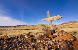 Ghost Town Grave Site. Old wooden cross marks a lone grave at an old ghost town Stock Photo