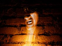 Ghost in the Walls. A horror background of a vampire coming alive in a brick wall for halloween royalty free stock photography