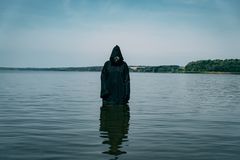 Ghost is in the water in a black cloak in the afternoon. The phantom looks creepy stock photography