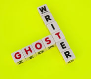 Ghost writer. Text ' ghost ' and ' writer ' inscribed in uppercase letters on small white cubes and arranged in crossword style with common letter ' t ', yellow stock image