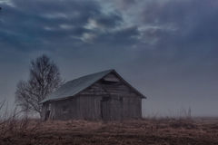 Ghostly Barn House. A barn house on the spring field on a very foggy night. The fog creates a spooky athmosphere Royalty Free Stock Image