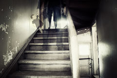 Ghostly figure in a hounted house. Ghostly figure standing on stairs inside a hounted house holding doll Stock Photo