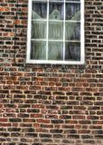 A ghostly figure looking out from an old window. On a red brick built building stock photos