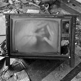 Ghostly figure on vintage tv set. A ghostly figure appears on the flickering screen of an old tv set. Haunted house Royalty Free Stock Photo