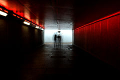 Ghostly figures in London underpass. Long exposure in London underpass shows ghostly silhouettes of people walking through with red lighting Royalty Free Stock Images
