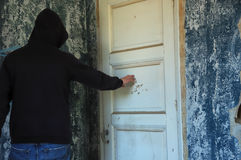 Ghostly hooded figure. By the closed door of a decayed room. Abandoned house interior Royalty Free Stock Images