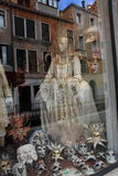 Ghostly Images in Venice, Italy. Reflections of buildings in a shop window in Venice, Italy, Europe.  Venetian masquerade masks and costume in the window give Royalty Free Stock Image
