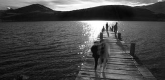 Ghostly jetty. Monochrome image of a jetty with ghostly figures moving around Stock Photo