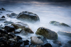 Ghostly Rocks Shoreline. Several type and size of rocks on the shoreling covered with moss with ghostly sea water wandering around them. Shoreline located in the Royalty Free Stock Images
